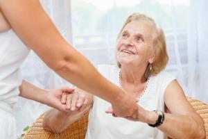 Idosa sentada numa cadeira a receber apoio domiciliário de uma senhora para a qual olha e sorri