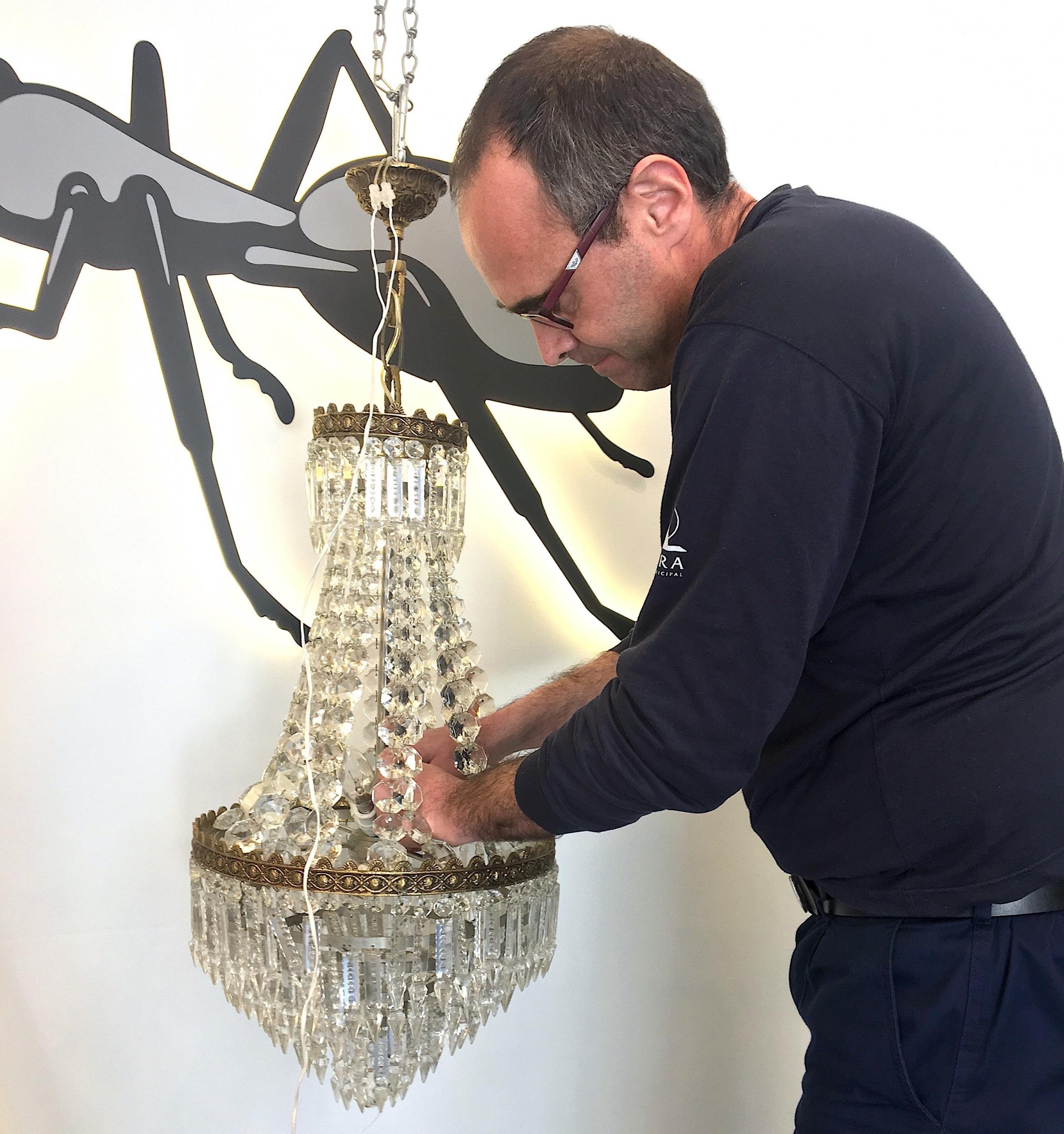 Homem prestando apoio domiciliário através da reparação de um candeeiro