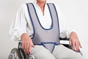 Idoso sentado numa cadeira de rodas utilizando um cinto específico de segurança cinzento
