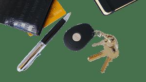Conjunto de objetos entre os quais uma botoneira, chaves, caneta, carteira, cartão e um bloco