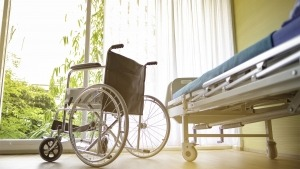 Paisagem vista do interior de um quarto onde está uma maca e uma cadeira de rodas
