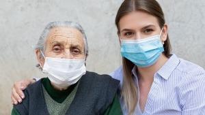 Idoso e uma rapariga jovem, ambos de máscara cirúrgica, olhando frontalmente