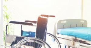 Imagem ligeiramente encadeada pelo sol com presença de uma cadeira de rodas e uma maca
