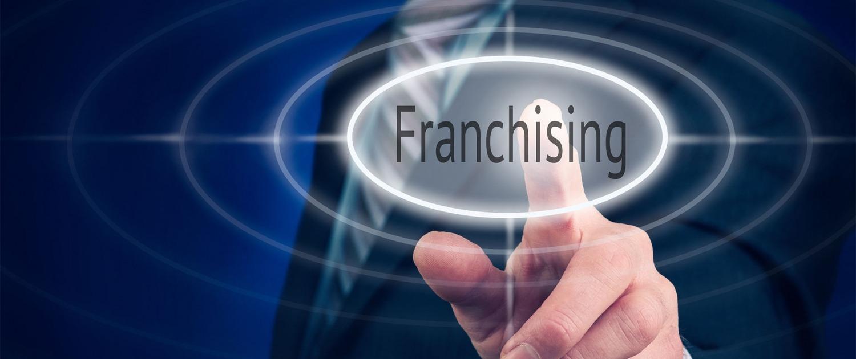 """Grande plano do dedo indicador de uma pessoa a clicar num ícone com a palavra """"Franchising"""""""