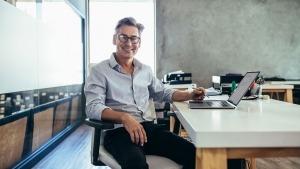 Homem sentado numa cadeira giratória, a sorrir, com uma caneta na mão e em frente a um computador