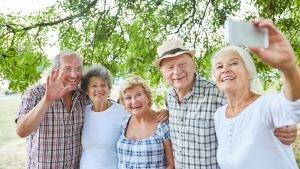 Cinco idosos juntos na rua a pousar, sorridentes, para uma selfie num smartphone