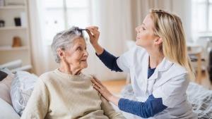 Técnica a prestar apoio domiciliário a uma idosa, penteando-lhe o cabelo com um pente