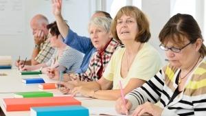 Seis idosos a realizar uma atividade com utilização de lápis em papel. Um deles tem o braço no ar