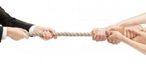 Várias pessoas puxando uma corda para dois lados diferentes. De um lado duas mãos, do outro seis