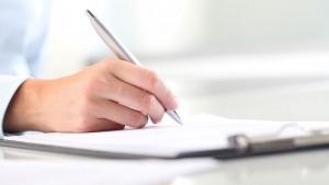 Grande plano da mão de uma pessoa, pegando numa caneta prateada, a escrever