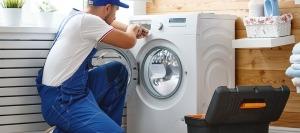 Homem prestando auxílio domiciliário ao reparar uma máquina de lavar roupa com uma chave apropriada