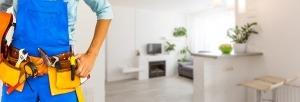 Pessoa numa casa com um cinto amarelo e castanho com várias ferramentas de reparação