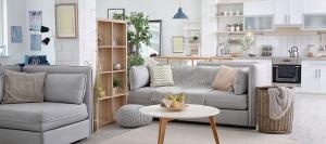 Plano sobre sala de estar e cozinha. Sofás, mesa e estante na sala. Vários utensílios na cozinha