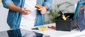 Homem a utilizar smartphone e com um cartão na outra mão. Caixa com ferramentas dentro e fora