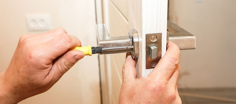 Plano apertado sobre pessoa a prestar apoio domiciliário consertando uma fechadura de porta