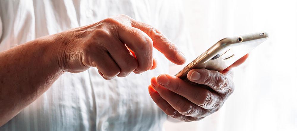 Plano apertado sobre mãos de uma pessoa a utilizar um smartphone