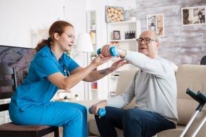 Técnica prestando apoio domiciliário a um idoso, ajudando-o a levantar um pequeno halter